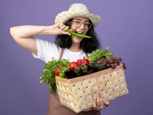Il giardiniere femminile giovane brunetta gioioso in occhiali ottici e in uniforme che indossa il cappello da giardinaggio tiene il cesto di verdure e finge di mordere il peperoncino isolato sul muro viola