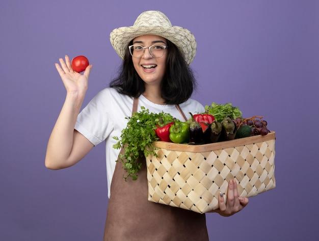 Il giardiniere femminile giovane brunetta gioioso in vetri ottici e in uniforme che indossa il cappello da giardinaggio tiene il cesto di verdure e il pomodoro isolato sulla parete viola