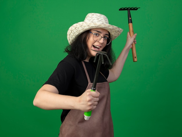 Joyful young brunette female gardener in optical glasses and uniform wearing gardening hat stands sideways holding rake and hoe rake isolated on green wall