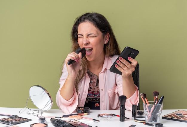 Радостная молодая брюнетка девушка сидит за столом с инструментами для макияжа, держит телефон и расческу, делая вид, что поет