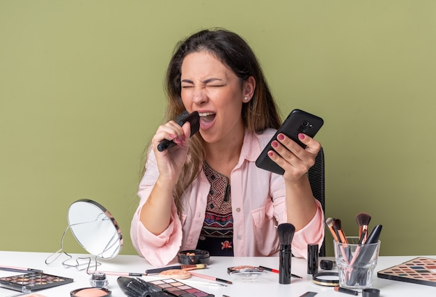 Joyful young brunette girl sitting at table with makeup tools holding phone and comb pretending to sing
