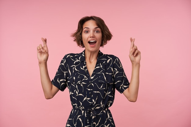Joyful young brunette lady with short haircut raising hands with crossed index fingers, making wish and looking with wide eyes and mouth opened, isolated