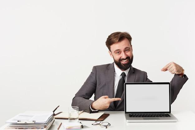 モダンなラップトップで作業台に座って、人差し指で画面を指して、広い笑顔で正面を幸せに見て、フォーマルな服を着たうれしそうな若いブルネットの男