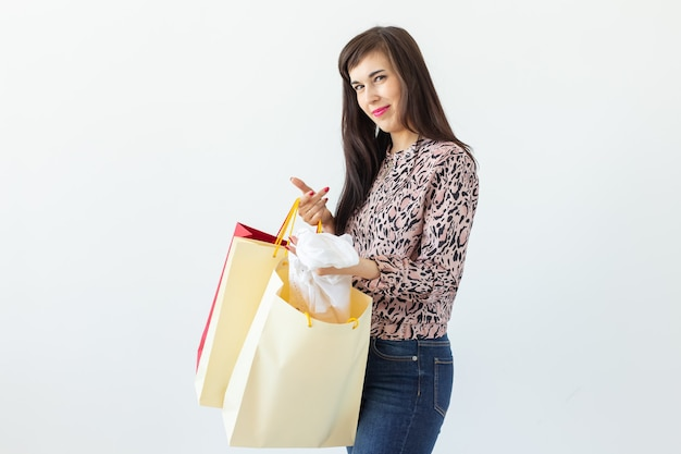 Joyful young brunette woman holding shopping bags posing on a white surface. concept of discounts