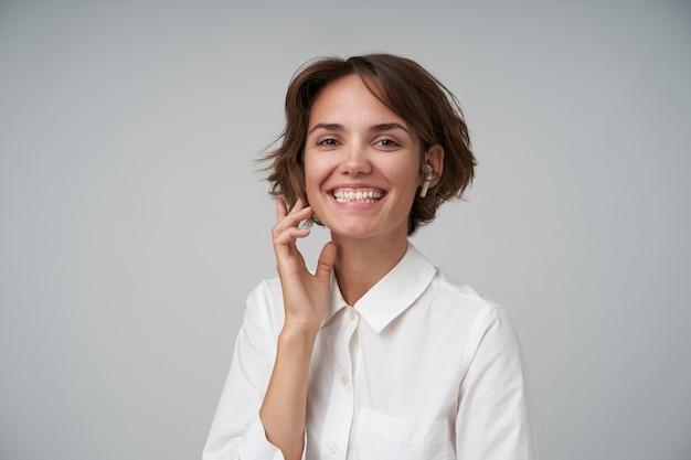 Радостная молодая брюнетка с повседневной прической, нежно касаясь ее лица и широко улыбаясь, показывая свои приятные эмоции, позирует