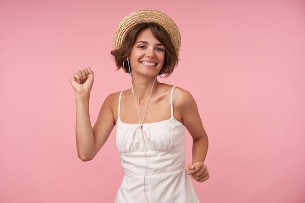 짧은 머리가 넓은 미소로보고 이어폰을 착용하고 훌륭한 음악을 즐기고 춤을 추는 즐거운 젊은 갈색 머리 여자