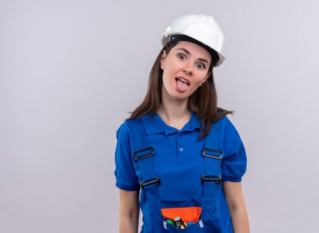 Ragazza allegra giovane costruttore con casco di sicurezza bianco e uniforme blu guarda la telecamera su sfondo bianco isolato con spazio di copia