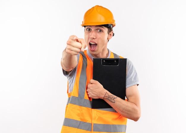 あなたにジェスチャーを示すクリップボードを保持している制服を着たうれしそうな若いビルダー男