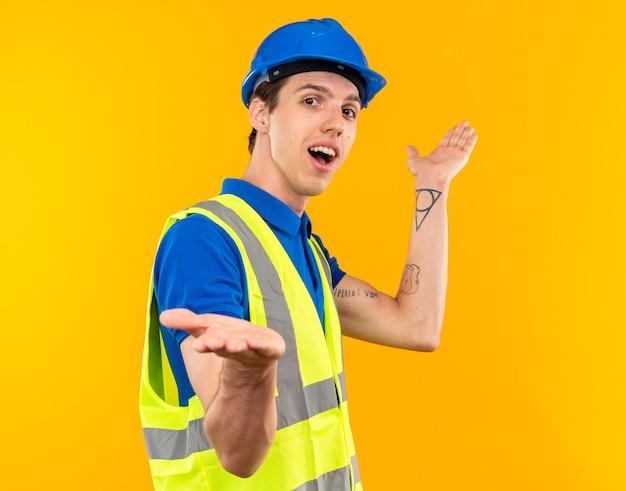 Радостный молодой строитель человек в униформе, разводя руками