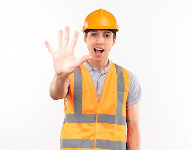 Joyful young builder man in uniform showing five