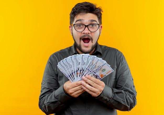 노란색 배경에 고립 된 돈을 들고 안경을 쓰고 즐거운 젊은 사업가