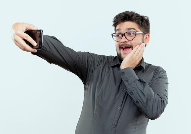 안경을 쓰고 즐거운 젊은 사업가 셀카를 가지고 흰색 배경에 고립 된 뺨에 손을 넣어