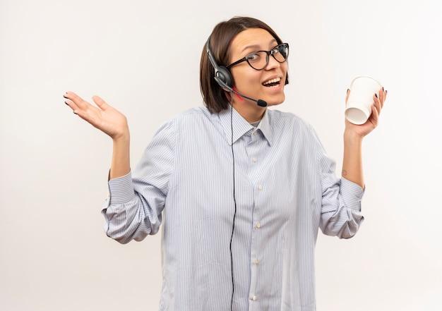 白で隔離の空の手を示すコーヒーカップを保持している眼鏡とヘッドセットを身に着けているうれしそうな若いコールセンターの女の子