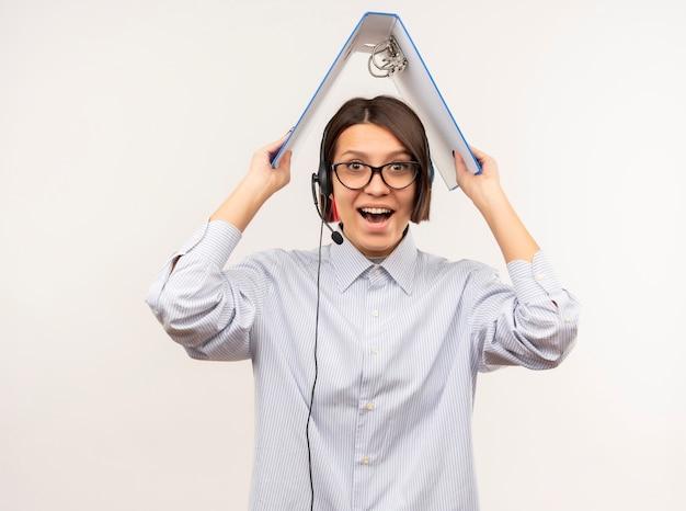 白で隔離の頭の上のフォルダーとヘッドセットを保持している眼鏡とヘッドセットを身に着けているうれしそうな若いコールセンターの女の子
