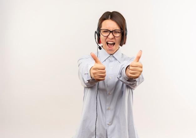 Радостная молодая девушка колл-центра в очках и гарнитуре показывает палец вверх с закрытыми глазами, изолированными на белом
