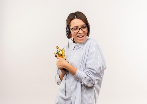 Gioiosa giovane ragazza della call center con gli occhiali e auricolare tenendo la coppa del vincitore guardando verso il basso isolato su bianco