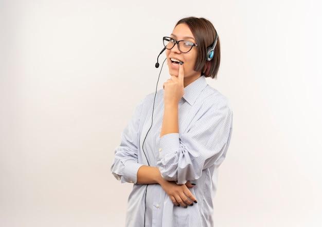 Gioiosa giovane ragazza call center con gli occhiali e auricolare mettendo il dito sul labbro isolato su bianco