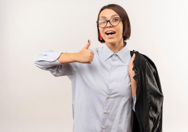 엄지 손가락을 보여주는 어깨에 그녀의 재킷을 들고 안경을 쓰고 즐거운 젊은 콜센터 소녀는 흰색에 고립
