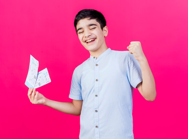 Радостный молодой кавказский мальчик, держащий билеты на самолет, делает жест да с закрытыми глазами, изолированные на малиновом фоне