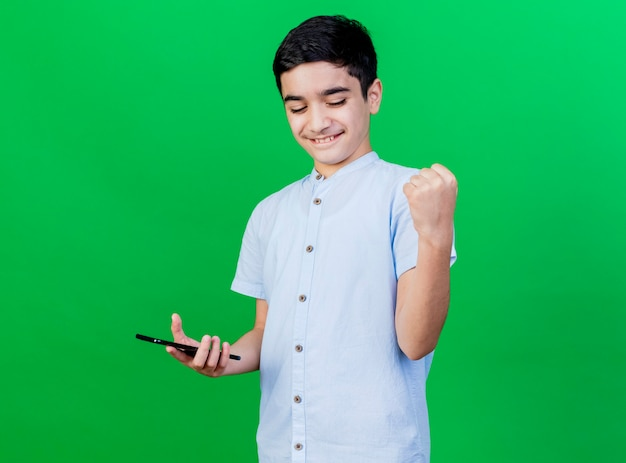 Joyful young caucasian boy holding mobile phone doing yes gesture isolated on green wall with copy space