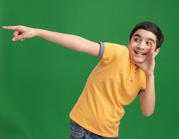 Gioioso giovane ragazzo caucasico che tiene la mano vicino alla bocca guardando e indicando il lato sussurrando isolato sul muro verde