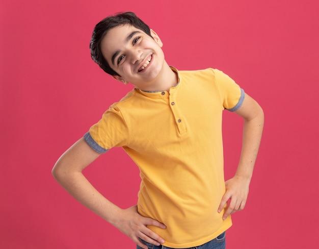 Joyful young caucasian boy keeping hands on waist