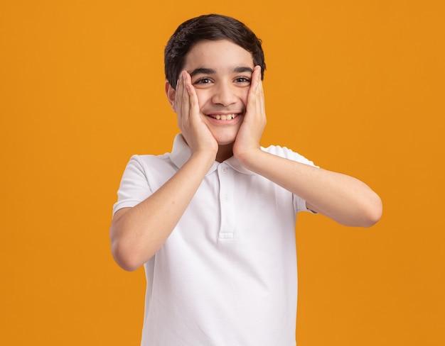 Радостный молодой кавказский мальчик кладет руки на лицо, глядя прямо, изолированное на оранжевой стене с копией пространства