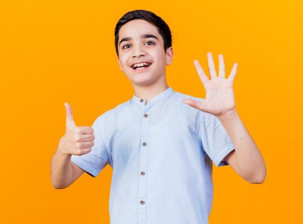 오렌지 배경에 고립 된 카메라를보고 손으로 6을 보여주는 즐거운 어린 백인 소년
