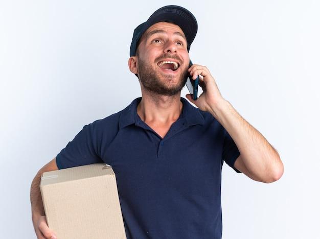 Gioioso giovane fattorino caucasico in uniforme blu e cappuccio con scatola di cartone che parla al telefono guardando in alto isolato sul muro bianco