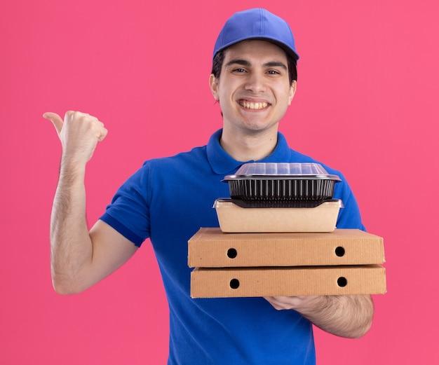 Gioioso giovane fattorino caucasico in uniforme blu e cappuccio che tiene i pacchetti di pizza con contenitore per alimenti e pacchetto di cibo di carta su di essi rivolto a lato