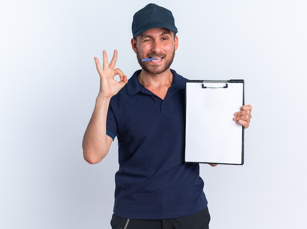 Joyful young caucasian delivery man in blue uniform and cap showing clipboard doing ok sign holding pen in mouth winking