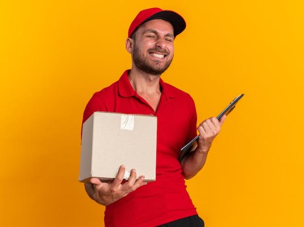 빨간색 유니폼을 입은 즐거운 백인 배달원과 주황색 벽에 눈을 감고 마분지 상자와 클립보드를 들고 있는 모자 프리미엄 사진