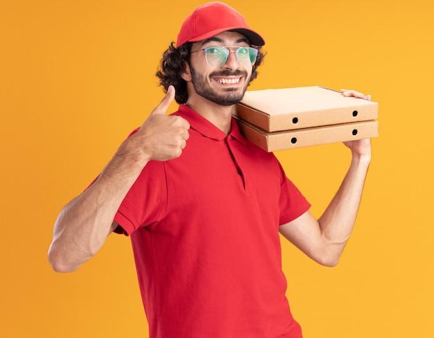 Радостный молодой кавказский доставщик в красной форме и кепке в очках, стоящий в профиле, держа пакеты с пиццей на плече, показывая большой палец вверх изолированным на оранжевой стене