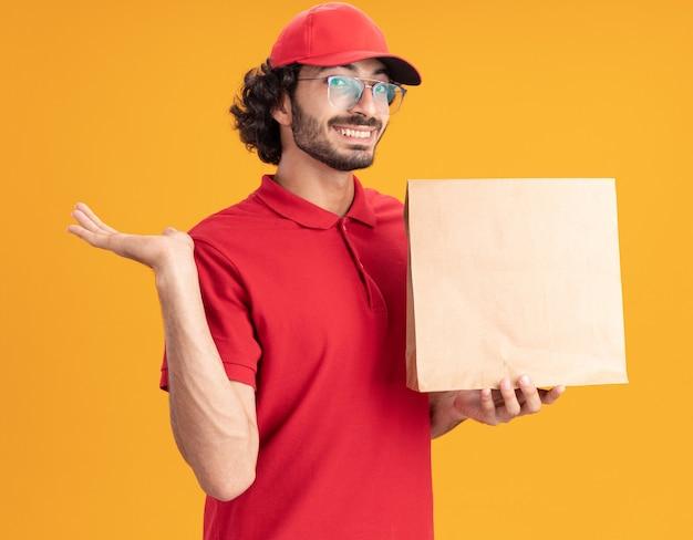 Gioioso giovane fattorino caucasico in uniforme rossa e berretto con gli occhiali che tengono il pacchetto di carta che mostra la mano vuota isolata sulla parete arancione