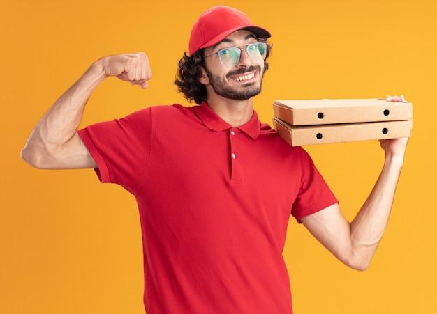 Gioioso giovane fattorino caucasico in uniforme rossa e berretto con gli occhiali che tengono i pacchetti di pizza facendo un gesto forte