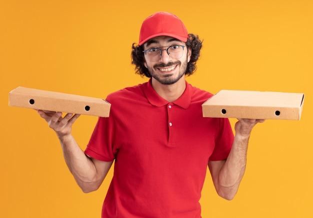 Gioioso giovane fattorino caucasico in uniforme rossa e berretto con gli occhiali che tengono i pacchetti di pizza