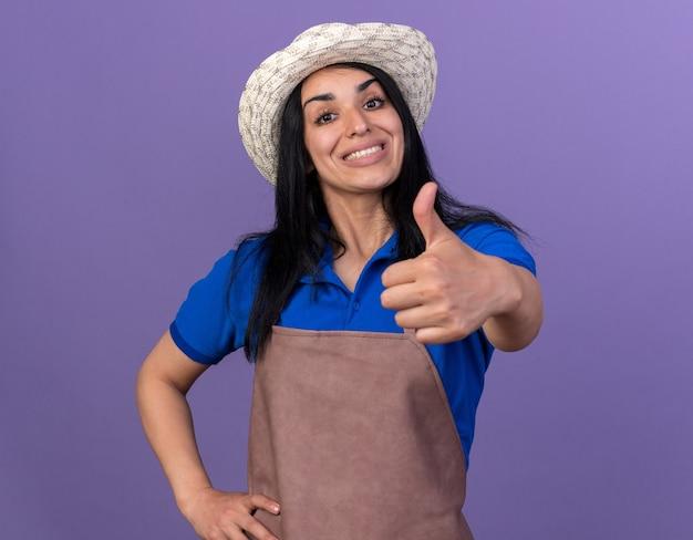 Gioiosa giovane giardiniera caucasica ragazza che indossa l'uniforme e il cappello che tiene la mano sulla vita che mostra il pollice in alto isolato sul muro viola