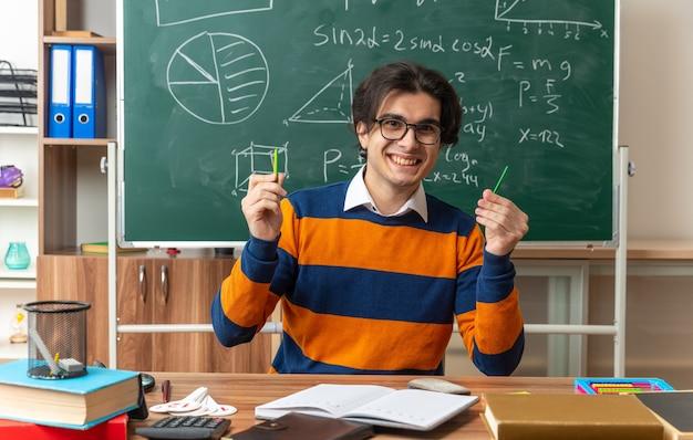 Gioioso giovane insegnante di geometria caucasica con gli occhiali seduto alla scrivania con materiale scolastico in classe guardando la parte anteriore che mostra i bastoncini di conteggio
