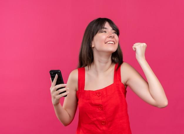 電話を保持し、コピースペースで孤立したピンクの背景に横を見て拳を保持しているうれしそうな若い白人の女の子