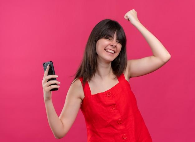 電話を保持し、孤立したピンクの背景に目を閉じて拳を上げるうれしそうな若い白人の女の子