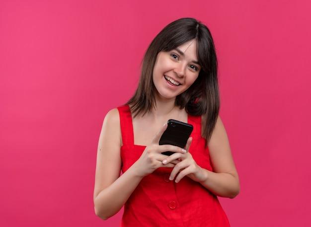 両手で電話を保持し、コピースペースで孤立したピンクの背景にカメラを見てうれしそうな若い白人の女の子