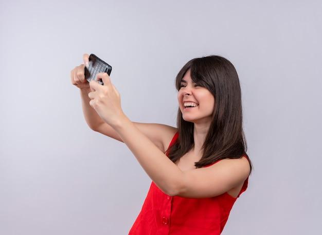 両手で携帯電話を保持し、孤立した白い背景の上の携帯電話を見てうれしそうな若い白人の女の子