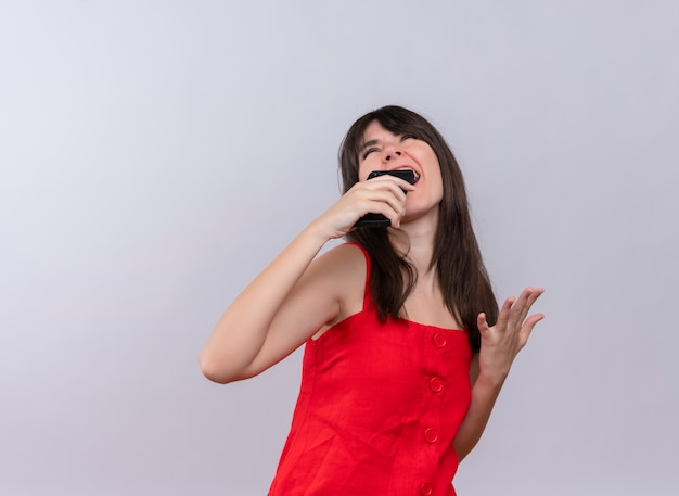 Gioiosa giovane ragazza caucasica tenendo il telefono con la mano aperta e alzando lo sguardo su sfondo bianco isolato con copia spazio