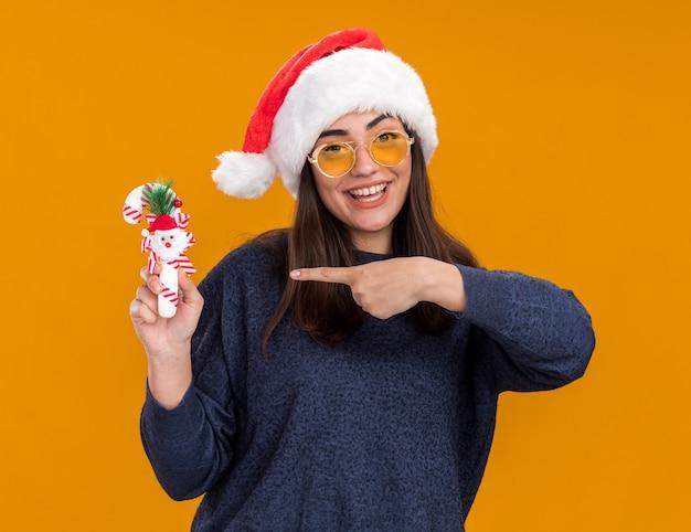 Радостная молодая кавказская девушка в солнцезащитных очках с санта-шляпой держит и указывает на конфету, изолированную на оранжевом фоне с копией пространства