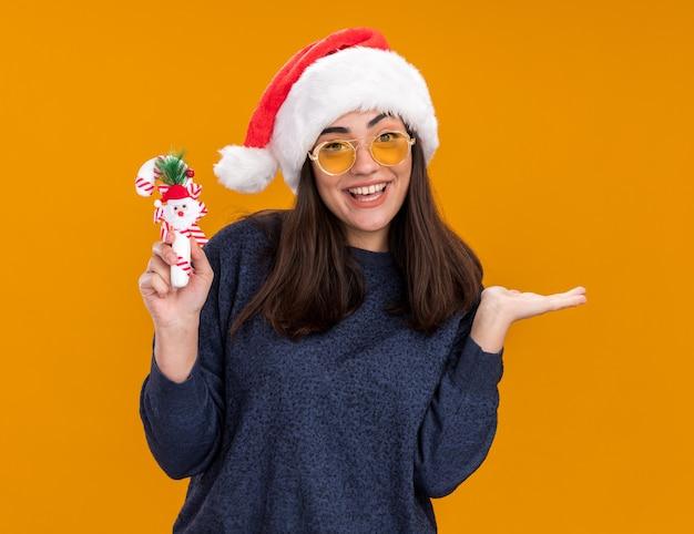 Радостная молодая кавказская девушка в солнцезащитных очках в шляпе санта-клауса держит конфету и держит руку открытой изолированной на оранжевой стене с копией пространства