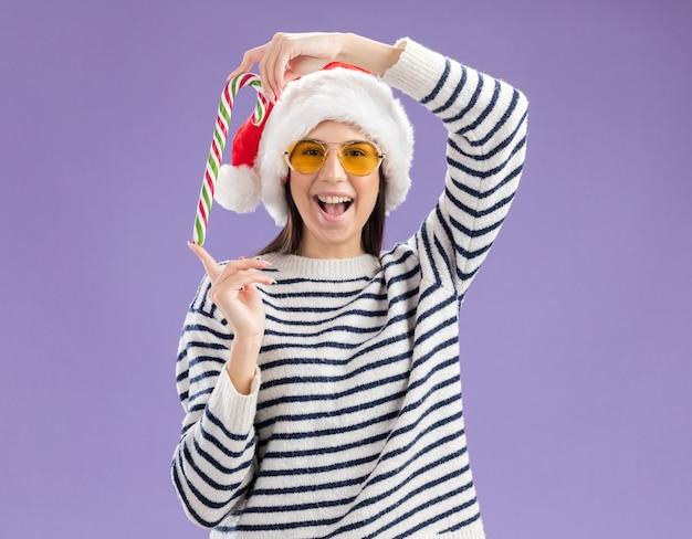 Радостная молодая кавказская девушка в солнцезащитных очках в шляпе санта-клауса держит конфету, изолированную на фиолетовом фоне с копией пространства