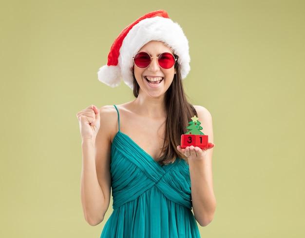 산타 모자와 태양 안경에 즐거운 젊은 백인 여자는 주먹을 유지하고 크리스마스 트리 장식을 보유