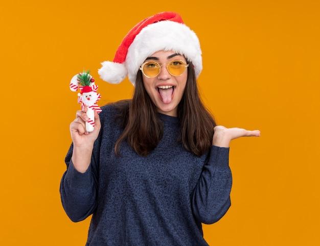 Радостная молодая кавказская девушка в солнцезащитных очках в шляпе санта-клауса высунула язык и держит конфету, изолированную на оранжевой стене с копией пространства