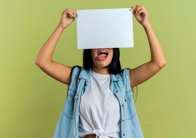 Gioiosa giovane ragazza caucasica tira fuori la lingua tenendo il foglio di carta davanti ai suoi occhi isolato su sfondo verde oliva con lo spazio della copia