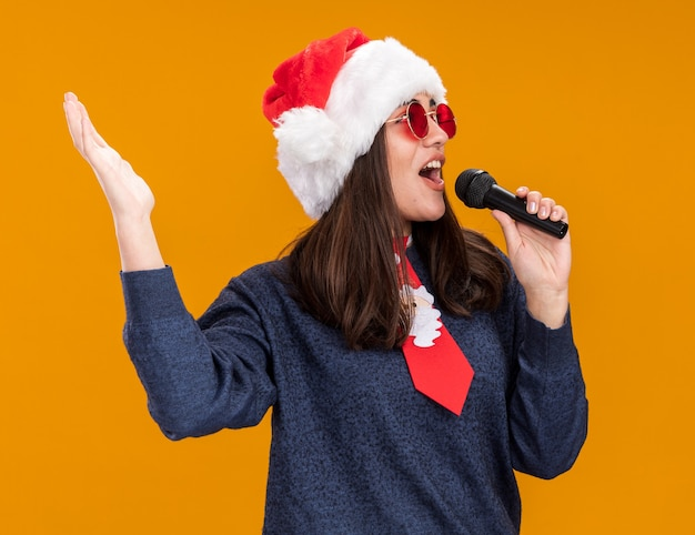 Joyful young caucasian girl in sun glasses with santa hat and santa tie holds mic pretending to sing looking at side isolated on orange wall with copy space